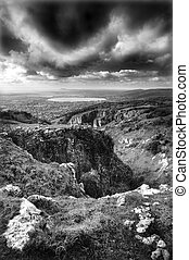 Beautiful monochrome image of stormy dramatic cloudy sky over 300 million year old rock landscape