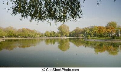 Beautiful morning sun shining over an urban park lake on a warm autumn day