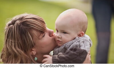 Beautiful mother and baby on a green lawn. Mom kissing baby playing with him.