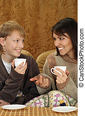 Beautiful mother and child sitting on the couch with a cup