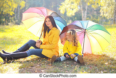 Beautiful mother and child with umbrella in autumn park