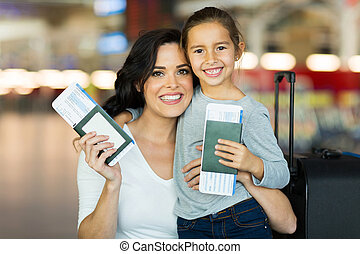 mother and daughter holding passports and boarding pass -...