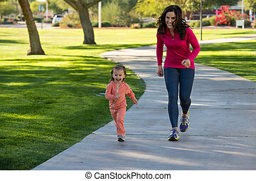 Beautiful mother and daughter running in the neighborhood -...