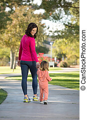 Beautiful mother and daughter walking in the neighborhood