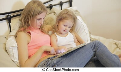 Beautiful mother and her daughter playing with tablet in the...