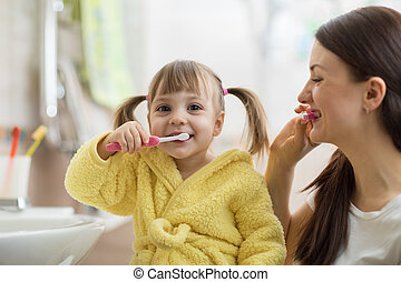 Beautiful mother and kid brushing teeth in bathroom