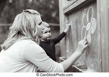 Beautiful mother and son drawing on blackboard with chalk