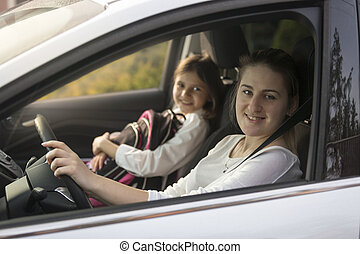 Beautiful mother driving car with daughter to school