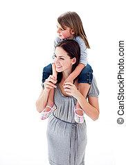 Beautiful mother giving her daughter piggyback ride