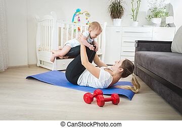 Beautiful mother holding baby and practicing yoga -...