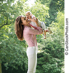 Beautiful mother holding cute baby in the park