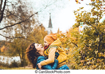 Beautiful mother holding her disabled son at park