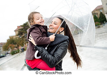 Beautiful mother holding her little daughter under the umbrella.