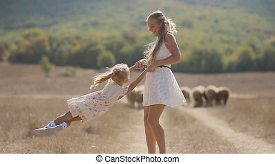Beautiful mother in light dress holding her little daughter by the hands and turning her in slow motion