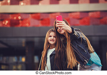 mother is making a selfie with her little daughter