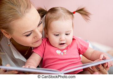 Beautiful mother is showing images in book to her little baby daughter at home.