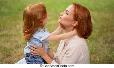 Beautiful mother kisses her child outdoor - Charming Mother...