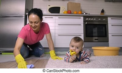 Beautiful mother on knees washing floor near baby -...