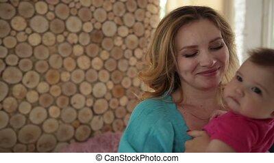 Beautiful mother rocking her baby girl to sleep -...
