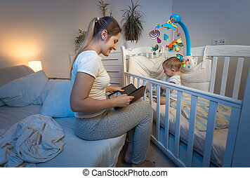 Beautiful mother sitting at baby's crib and reading a book