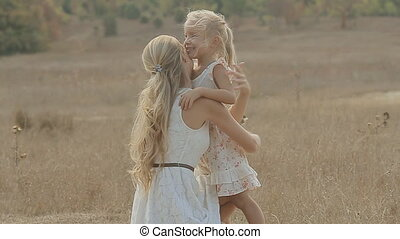 Beautiful mother sitting next to her little daughter and kissing her in the middle of the field