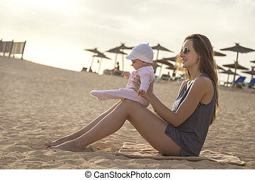 mother sitting on the beach with her daughter