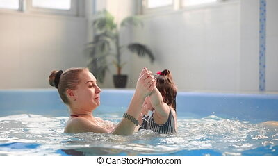 Beautiful mother teaching cute baby girl how to swim in a swimming pool. Child having fun in water with mom.