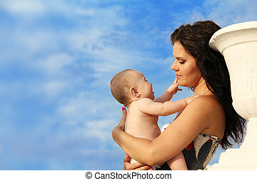 Beautiful Mother with baby over blue sky