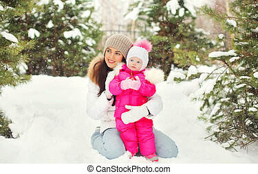 Beautiful mother with child in snowy winter day on snow