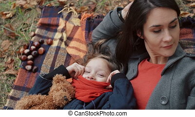 beautiful mother with her cute little daughter lying on the plaid playing with maple leaves in autumn park 4k