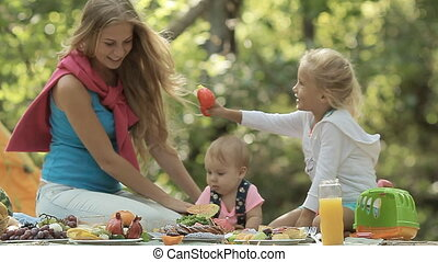 Beautiful mother with her little daughters on the nature on picnic