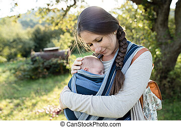 Beautiful mother with her son in sling, green nature