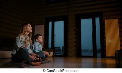 Beautiful mother with her son playing video games on gaming console in the living room of his house. Happy family in a country house.