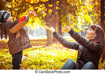 Beautiful mother with son in autumn park