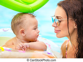 Beautiful mother with son in the pool