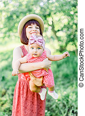 Beautiful Mother with the straw hat And her little daughter outdoors family look in in a pink dress . Outdoor Portrait of happy family. family look. Happy mother having fun with her daughter