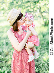 Beautiful Mother with the straw hat And her little daughter outdoors family look in in a pink dress . Outdoor Portrait of happy family. family look. mom kisses daughter in a cheek.