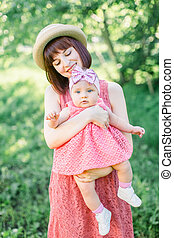 Beautiful Mother with the straw hat And her little daughter outdoors family look in in a pink dress . Outdoor Portrait of happy family. family look. Positive human emotions, feelings, emotions.