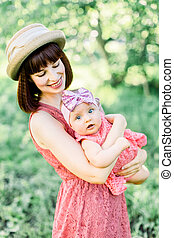 Beautiful Mother with the straw hat And her little daughter outdoors family look in in a pink dress . family look. Young mother throws up baby in the sky, on sunny day.