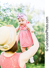 Beautiful Mother with the straw hat And her little daughter outdoors family look in in a pink dress . Young mother throws up baby in the sky, on sunny day.
