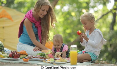 Beautiful mother with two charming little girls playing on a picnic