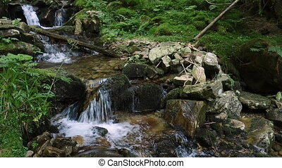 beautiful mountain creek flows over boulders with moss at...