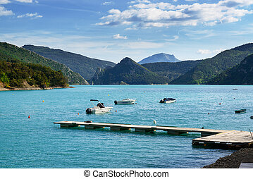 Beautiful lake in Southern Alps mountains, France, with pier and boats