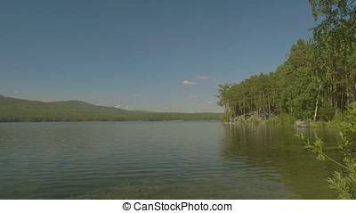 Beautiful mountain lake in the forest. Beautiful landscape with a lake. In the mirror surface of the water reflects the blue sky