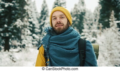 Beautiful mountains in winter time. Man with beard, wearing yellow winter clothes goes down the mountain road and looking at the camera
