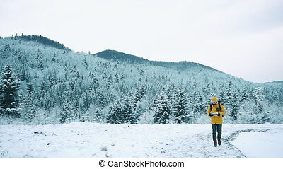 Beautiful mountains in winter time. Man with beard, wearing yellow winter clothes goes with a tourist map in hands, goes along the mountain road against the background of the winter landscape