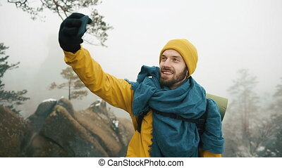 Beautiful mountains in winter time. Man with beard, wearing yellow winter clothes take selfie against the background of beautiful mountains