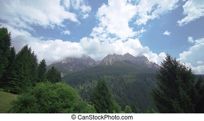 Beautiful mountains of rock covered by the white clouds of the blue sky with the green forest at the bottom