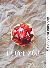 Beautiful muffin with fresh strawberries lies on the craft paper, the inscription I love you