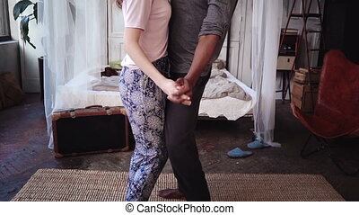 Beautiful multiethnic couple in pajamas dancing together and...